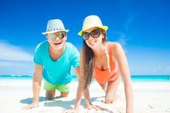 在明亮的坐在含沙热带海滩的衣裳和帽子的夫妇 免版税库存照片