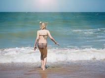 在明亮的太阳下的女孩在凉快的海水轻轻地设置 图库摄影