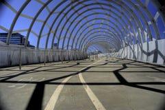 在明亮的太阳的脚和周期桥梁 免版税库存图片