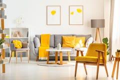 在明亮的客厅内部的黄色木扶手椅子与灰色 免版税库存图片