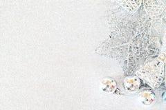 在明亮的抽象背景bokeh的发光的银色装饰品 图库摄影