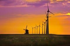 在明亮的日落前面的风车 免版税库存图片