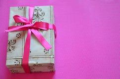 在明亮的桃红色,绯红色背景,顶视图的工艺包装纸当前箱子工艺绳索弓丝带 庆祝新 库存照片