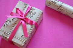 在明亮的桃红色,绯红色背景,顶视图的工艺包装纸当前箱子工艺绳索弓丝带 庆祝新 免版税图库摄影