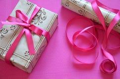 在明亮的桃红色,绯红色背景,顶视图的工艺包装纸当前箱子工艺绳索弓丝带 庆祝新 图库摄影