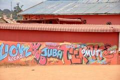 在明亮的橙色墙壁上的街道画在非洲 免版税图库摄影