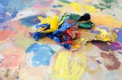 在明亮的油漆的艺术调色板 免版税库存图片