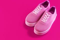 在明亮的紫红色的背景的桃红色运动鞋 免版税库存照片