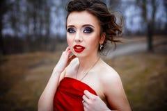 在明亮的红色丝绸折叠的女性 免版税库存照片