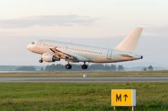 在明亮的红色日落期间,飞机飞行离开在一条跑道离开在晚上 免版税图库摄影