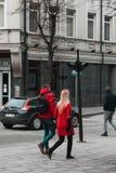 在明亮的红色穿戴的夫妇走在城市 库存图片