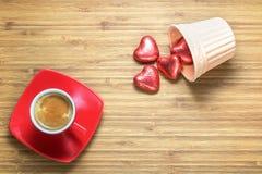 在明亮的红色箔包裹的心形的甜点在木纹理的一个陶瓷花瓶与红色杯子coffe在它附近 库存图片