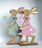在明亮的背景前面的两只木复活节兔子 库存图片