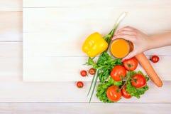 在明亮的背景的特写镜头菜 拿着一杯汁液的妇女 健康蕃茄和胡椒在一张木桌上 库存图片