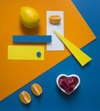 在明亮的背景蓝色橙黄三角圈子长方形几何心脏橘子果酱的柠檬桔子 免版税库存照片