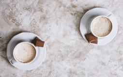 在明亮的葡萄酒背景的两个咖啡杯 库存图片