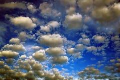 在明亮的蓝天的很多微小的灰色和棕色云彩由油 免版税库存照片