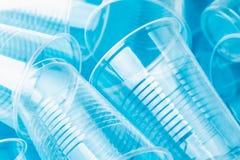 在明亮的蓝色背景的新的干净的空的透明一次性塑料玻璃 库存图片