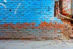 在明亮的蓝色颜色绘的老砖墙一半 免版税库存图片