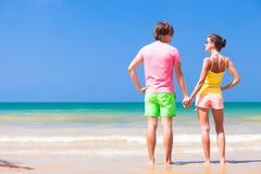 在明亮的衣裳的夫妇在热带海滩 图库摄影