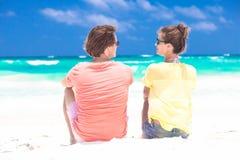 在明亮的衣裳的夫妇坐热带海滩 图库摄影