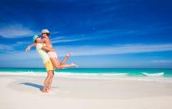 在明亮的衣裳的夫妇获得乐趣在热带 免版税库存图片