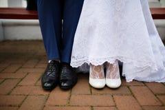 在明亮的衣裳的新娘和新郎在长凳 免版税库存照片