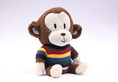 在明亮的镶边毛线衣的可爱的愉快的被充塞的猴子 免版税库存图片