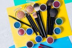 在明亮的黄色背景,顶视图,特写镜头,脸的专业化妆用品 库存图片