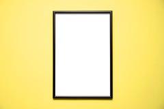 在明亮的黄色墙壁上的空白的黑框架 免版税图库摄影