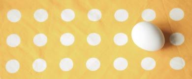 在明亮的黄色被加点的布料的一个鸡蛋 免版税库存图片