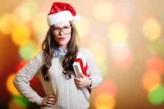 在明亮的bokeh注重的圣诞老人帽子的少妇 免版税库存照片