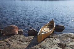 在明尼苏达北部湖岩石岸的独木舟日落的 免版税库存图片