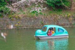 在明轮船的家庭骑马在东京Chidorigafuchi佐仓公园 免版税库存图片
