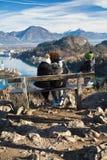 在星期天下午旅行的年轻家庭在放松在长凳的小山上面由风景视域惊奇了 图库摄影