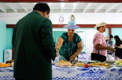 在星期日早晨茶的库克群岛妇女服务传统食物 免版税库存图片