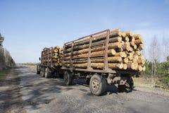 在春天在方式汽车的拖车运载两本日志 免版税图库摄影