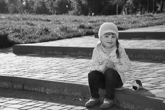在春天坐一个小女孩的步有玩具狗的 库存照片