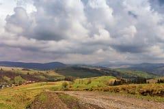 在春天小山的乡下公路 雨、云彩和阳光 免版税库存图片
