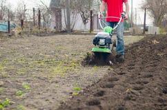 在春天有翻土机机器的庭院供以人员工作 图库摄影
