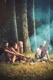 在春天森林徒步旅行者的野餐敬酒香肠在营火坐草甸在森林,旅行里 免版税库存图片