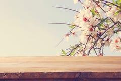 在春天樱花树前面的木土气桌 产品显示和野餐概念 库存照片