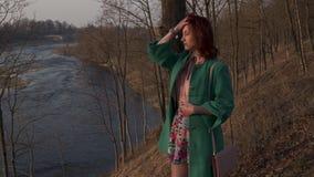 在春天河的年轻女人享用的和观看的日落 股票录像