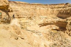 在春天湖上的人常设沙漠山峭壁边缘 免版税图库摄影