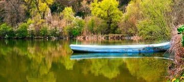 在春天湖的蓝色老小船 库存照片