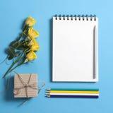 在春天的方形的笔记薄有与一朵黄色玫瑰的白色牛皮纸的在蓝色背景说谎 Copyspace 库存图片