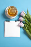 在春天的方形的笔记薄有白色牛皮纸的,桃红色郁金香和茶在蓝色背景 Copyspace 库存照片