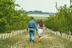 在春天的有吸引力的年轻愉快的夫妇从事园艺 免版税库存图片