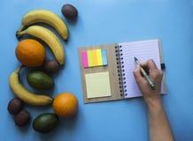 在春天笔记贴纸色的手上的一个蓝色背景笔记本上写笔把柄果子桔子香蕉鲕梨猕猴桃 库存照片