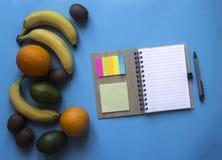 在春天笔记贴纸色的笔谎言果子桔子香蕉鲕梨猕猴桃的一个蓝色背景笔记本上 免版税库存图片